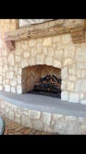 elevated-fireplace-with-cement-front-accent-and-wooden-shelfing-580x1030